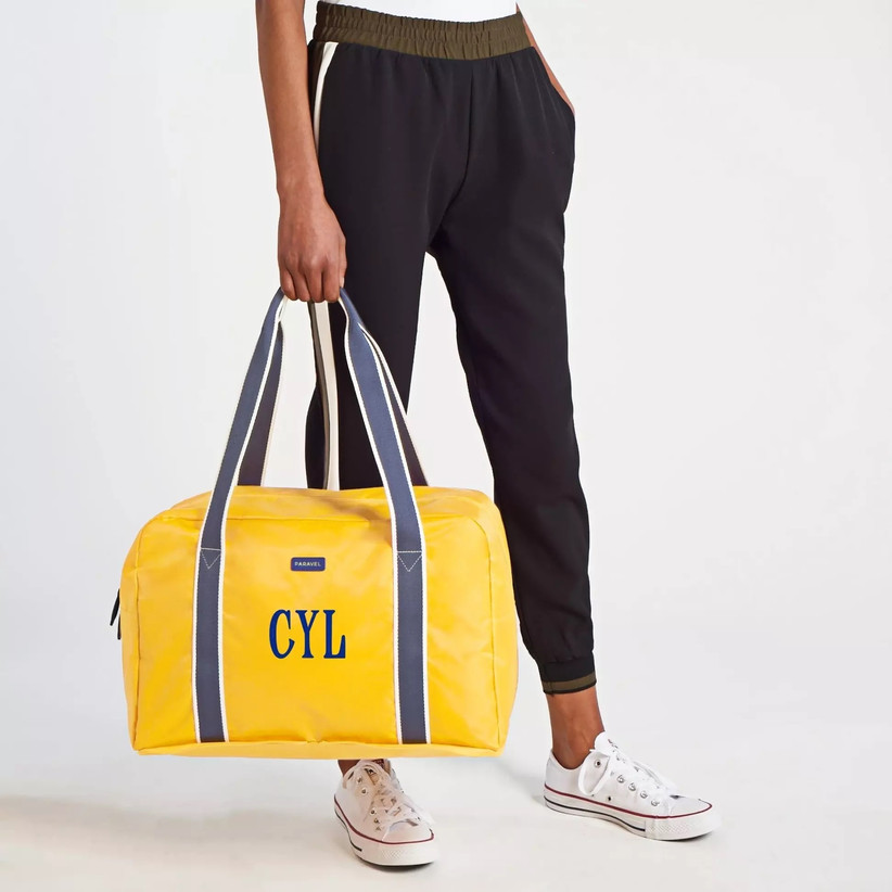 Woman holding yellow duffel bag with navy straps and navy monogram