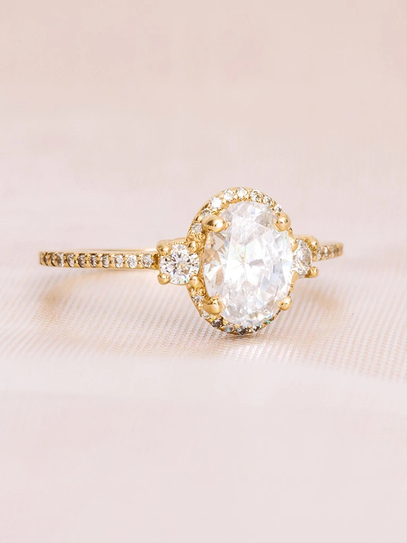 oval cut three stone engagement ring with yellow gold pave halo setting