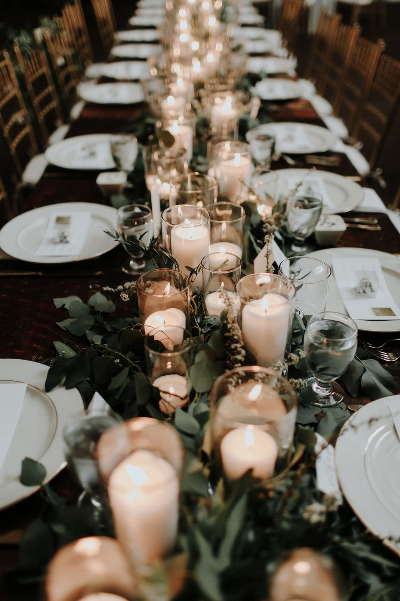 close-up of wedding centerpiece with greenery and assorted white candles in glass hurricane vases