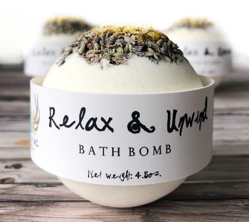 Lavender and chamomile bath bomb with pretty label around it reading Relax and Unwind