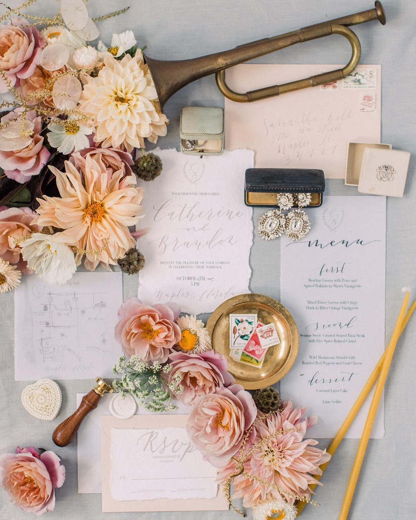 vintage-style wedding flat lay with invitations, flowers, and jewelry