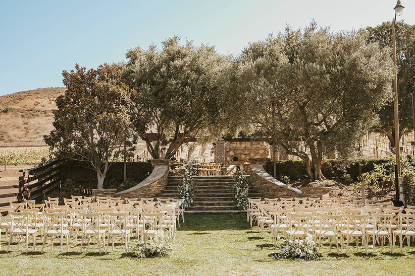 sunny grass courtyard with stone steps leading to ceremony altar on top of a hill with mountains in the background