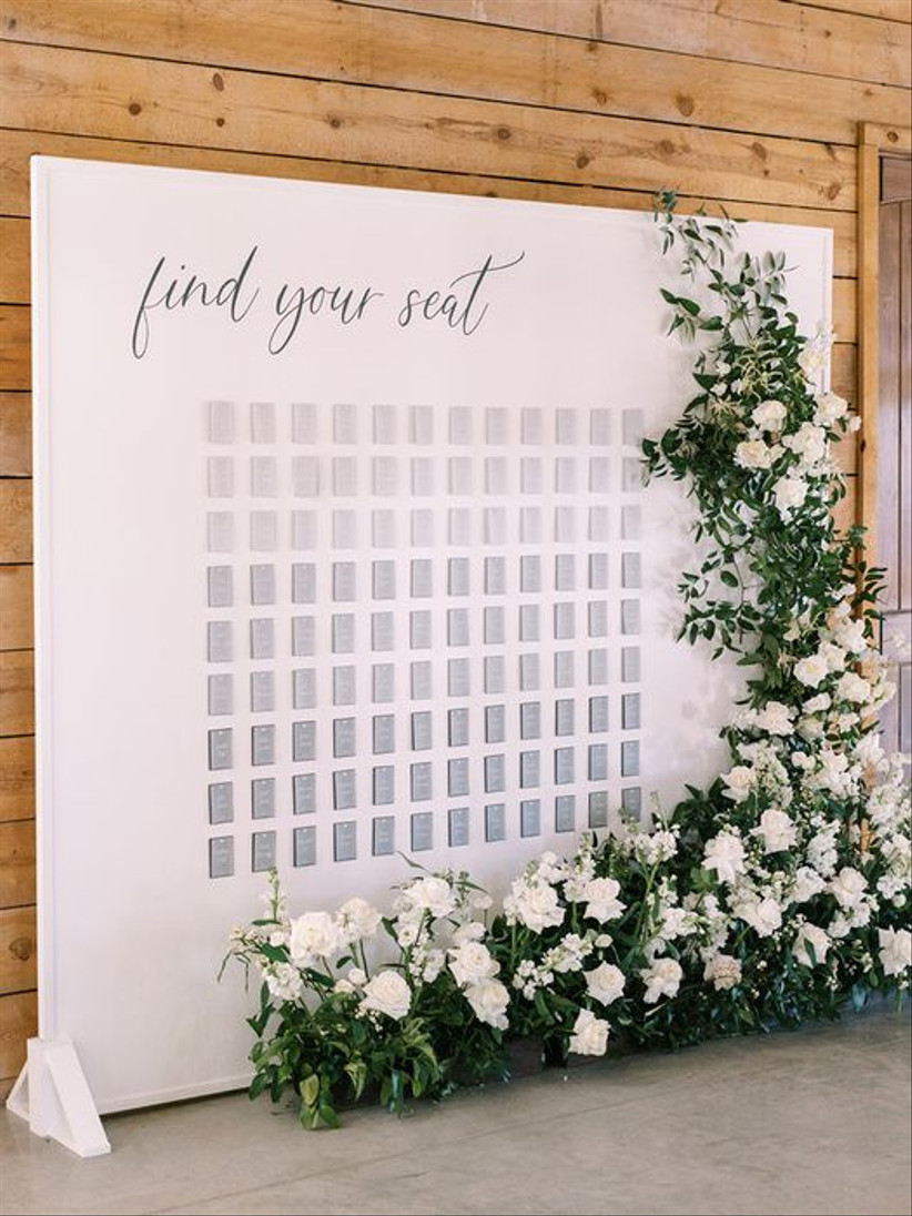 white wall with gray ombre wedding escort cards and fresh greenery