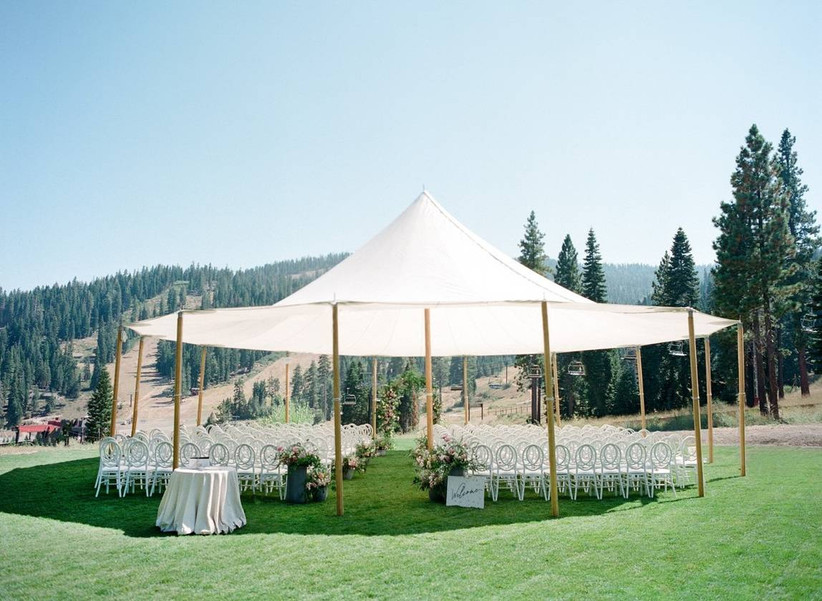 outdoor wedding ceremony covered by sailcloth tent with mountains and trees in the background
