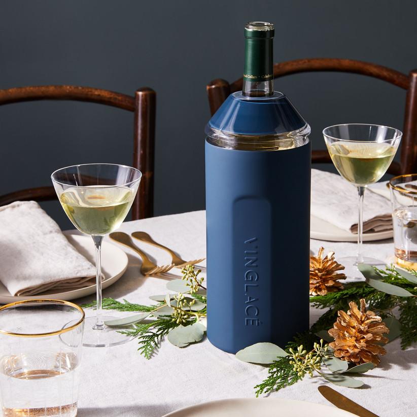 Navy wine bottle chiller containing bottle of wine on dinner table