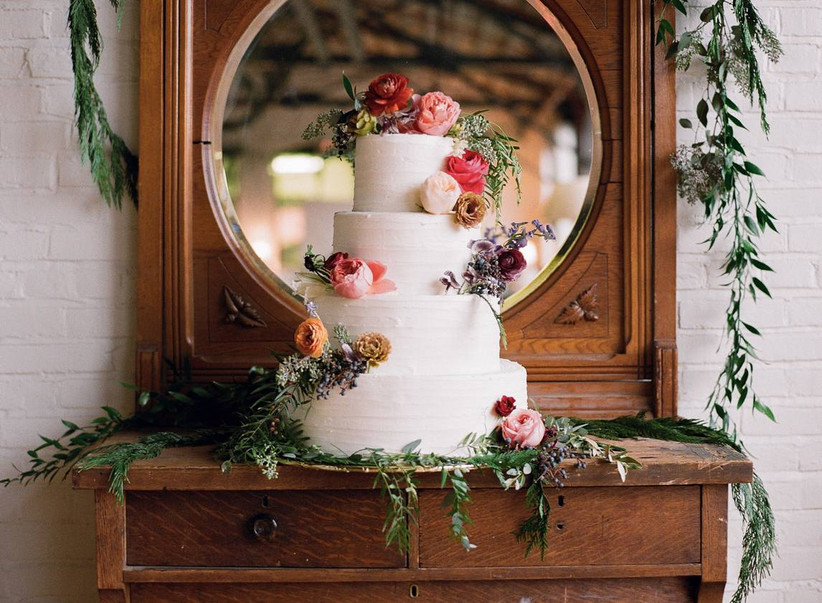 white wedding cake decorated with pink and yellow flowers is displayed on an antique wooden dresser