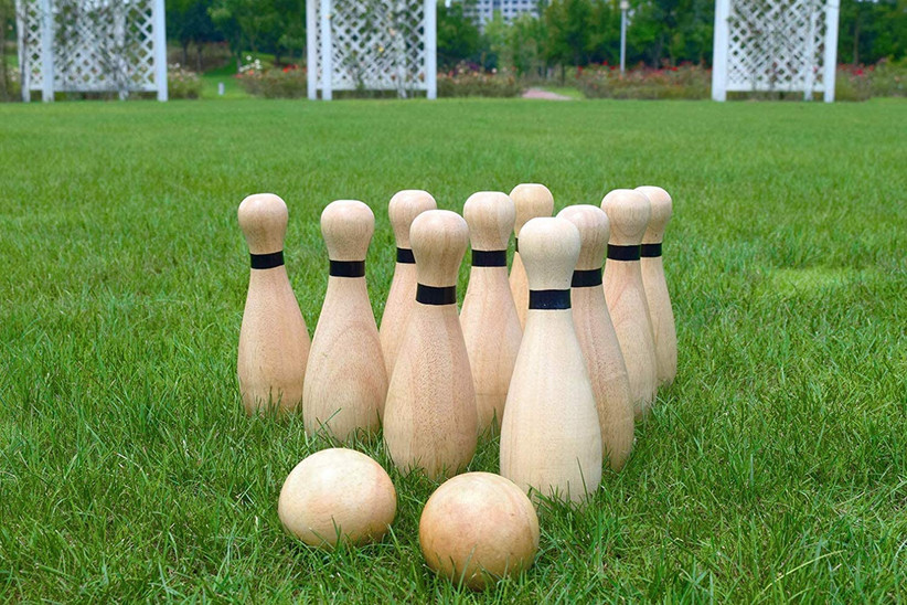 wooden bowling pins and balls on grass
