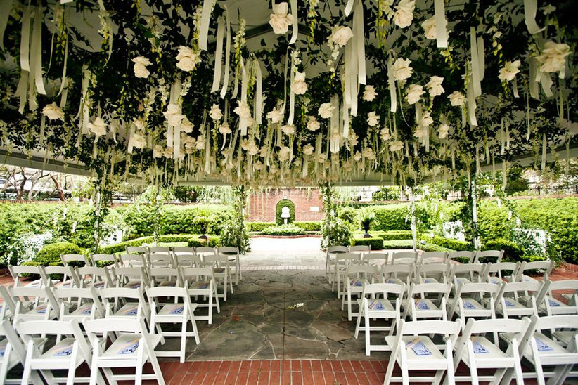 outdoor wedding ceremony space with beautiful white and green floral canopy and rows of folding chairs facing the altar