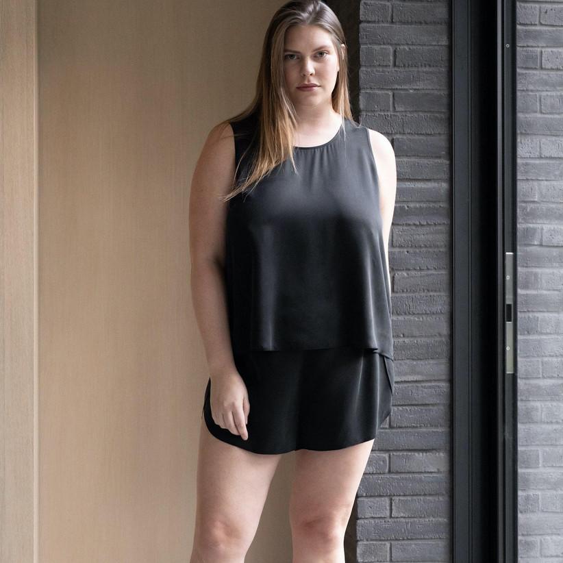 Plus-size model wearing black silk vest and short pajama set
