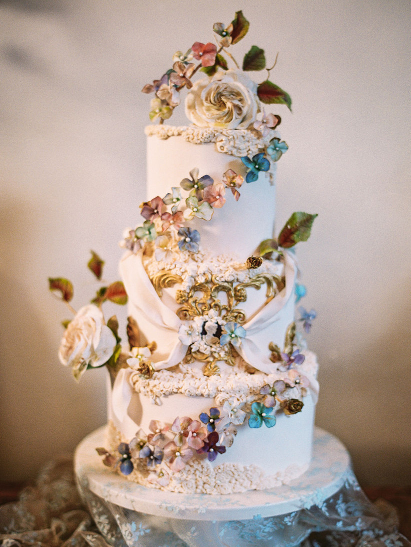 ornate wedding cake decorated with ombre sugar flowers and gold antique filigrees and scrollwork