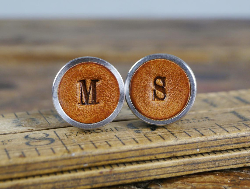 Two leather-inlay cuff links with the initials M and S