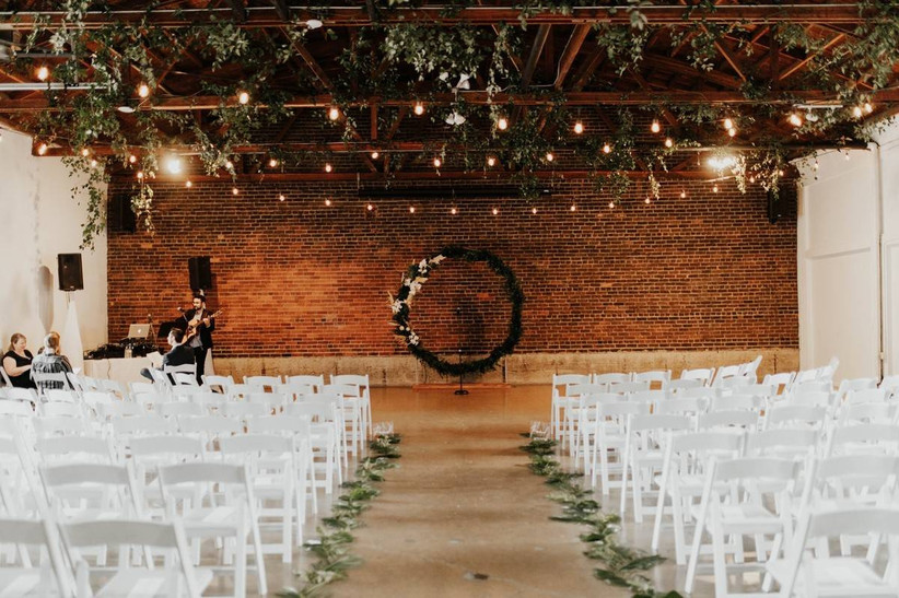 industrial wedding venue ceremony with brick wall as backdrop and large greenery wreath-style altar