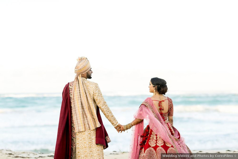south asian wedding couple holding hands on beach