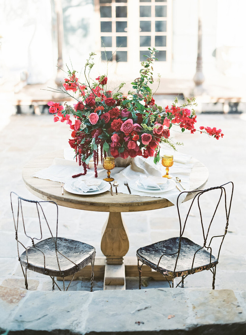 sweetheart table with oversized centerpiece of red roses and bougainvillea