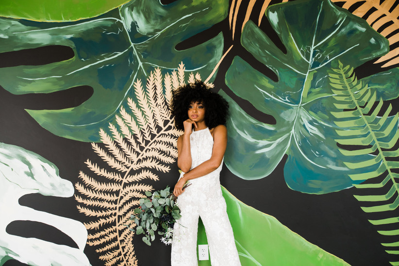 Black bride with natural hair stands in front of mural showcasing 2021 wedding colors oversized greenery leaves painted