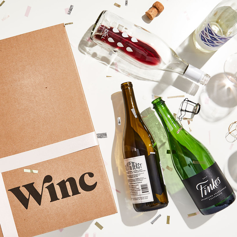 Winc delivery box next to empty wine bottles on a table with confetti