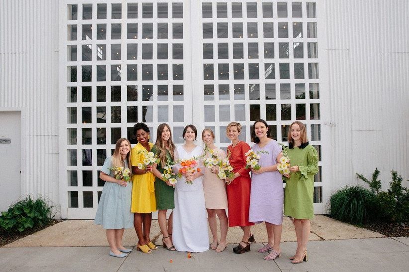 bride stands outside with her bridesmaids wearing green, yellow, red, and lilac dreses