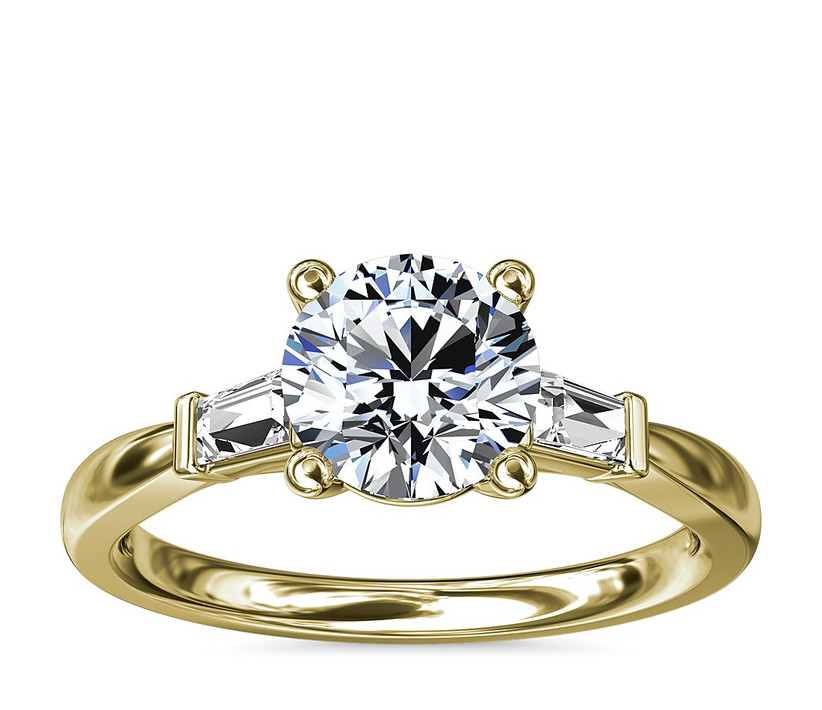 yellow gold three stone engagement ring with round diamond and baguettes
