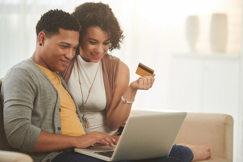 couple looking at computer while holding credit card