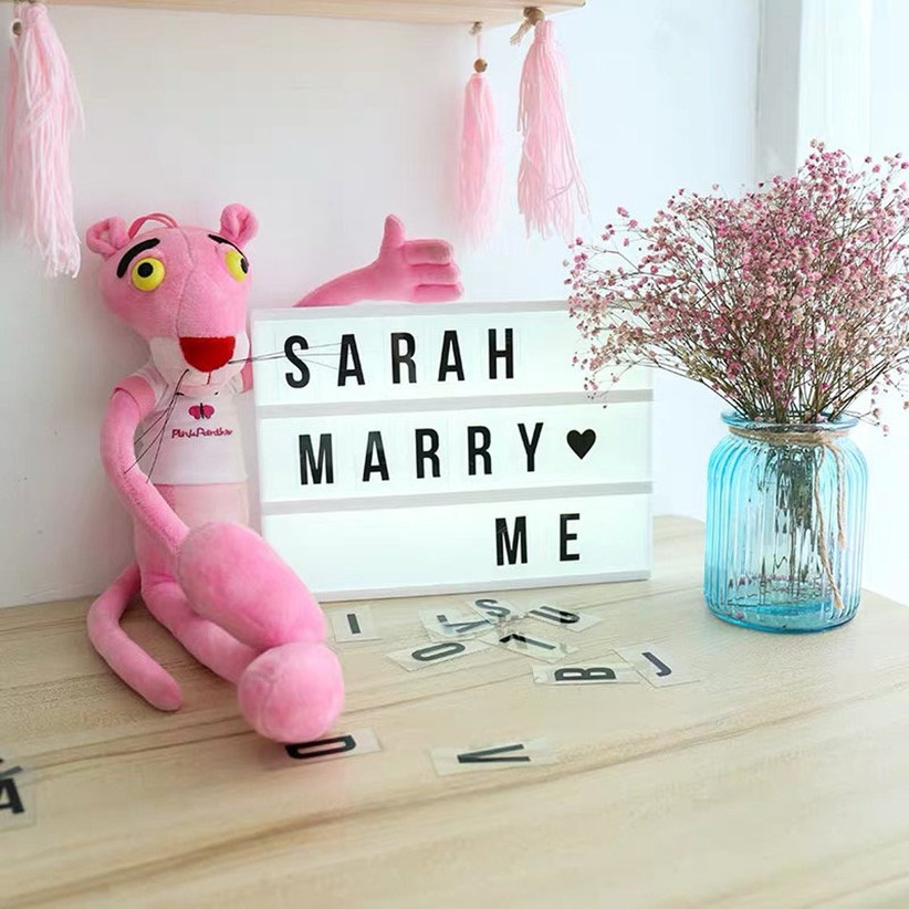 Marry Me cinema light box next to stuffed animal and flowers