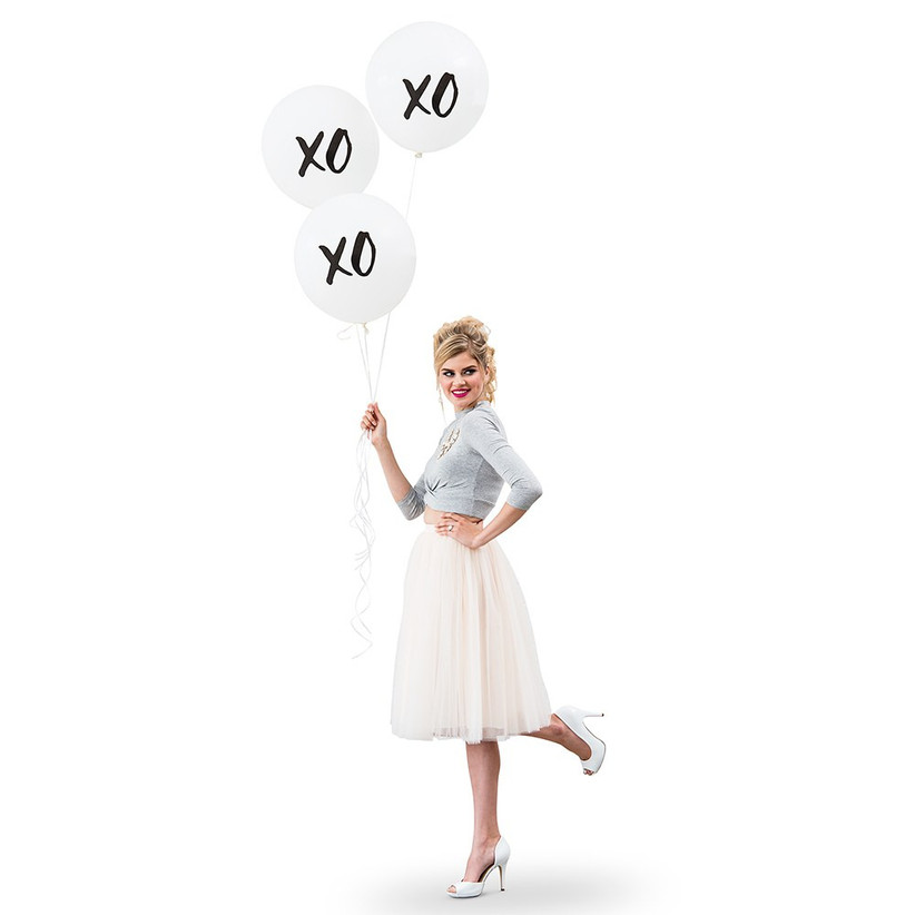Woman smiling holding three large XO balloons against a white backdrop