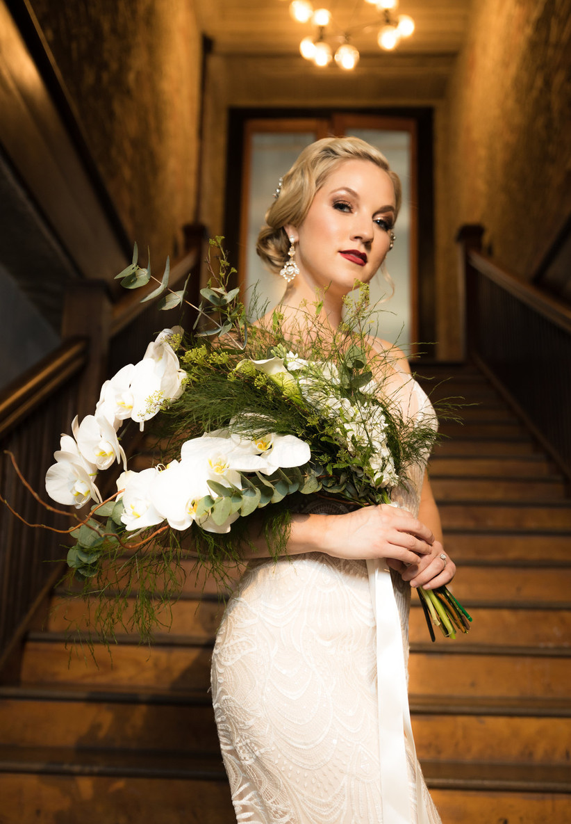 bride stands on staircase holding cascade wedding bouquet of white phalaenopsis orchids and greenery