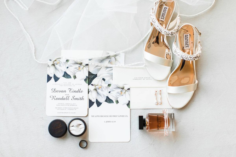 modern wedding flat lay with white high heels, perfume bottle and wedding rings