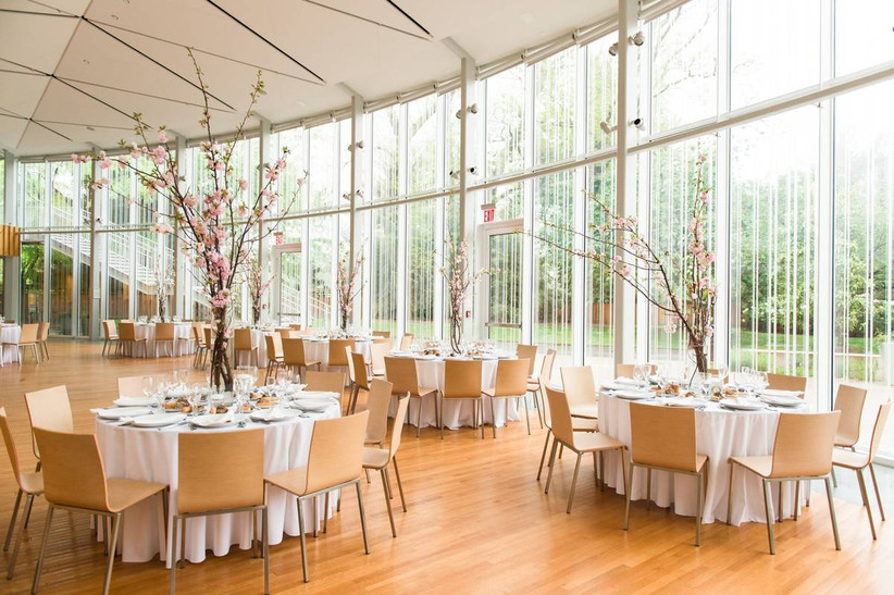 indoor botanical gardens wedding reception ballroom with wall of windows looking out into garden round tables decorated with pink cherry blossom branch centerpieces