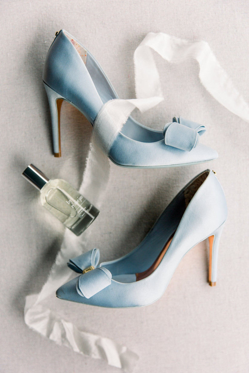 a pair of light blue satin shoes are turned on their side and photographed from above with a perfume bottle and ribbon also pictured