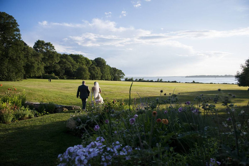 newlyweds walk through a garden and on the lawn overlooking the water at rhode island wedding venue