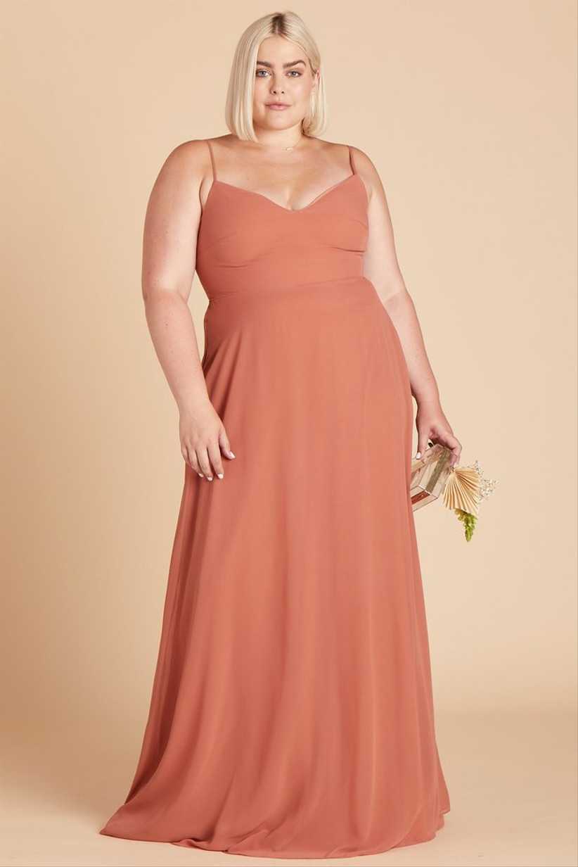 Plus-size model wears peach orange bridesmaid dress trend and carries a clear acrylic clutch purse