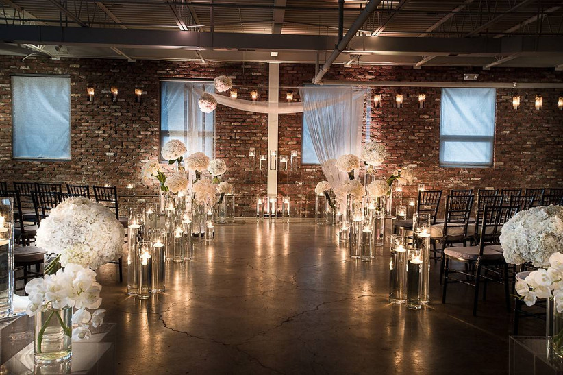 indoor wedding ceremony with brick wall backdrop white flowers and string lights