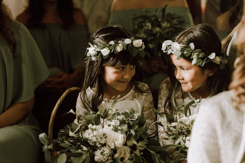 two flower girls wearing greenery crowns sit in chairs during the wedding ceremony and look at each other while giggling