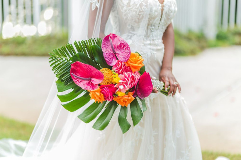 Black bride holds tropical beach wedding bouquet with monstera leaves and pink anthurium with orange roses