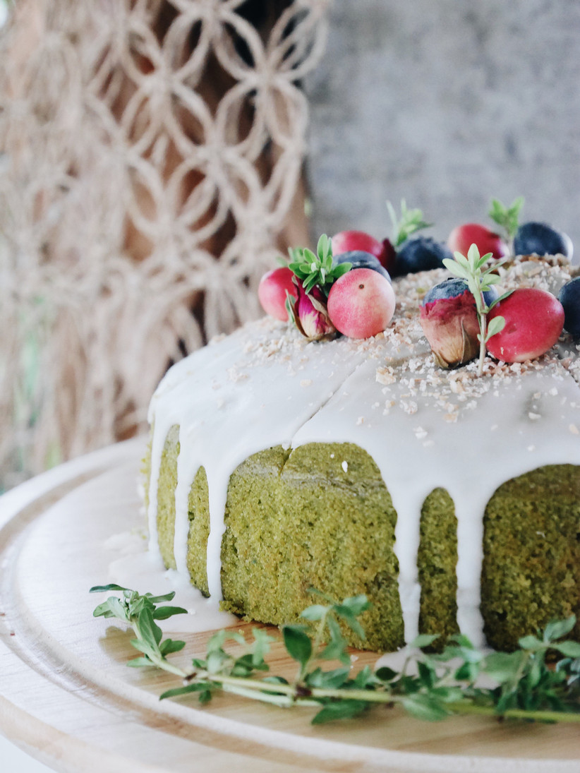 close-up of green tea matcha wedding cake topped with cranberries blueberries
