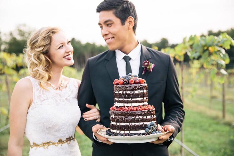 couple holding chocolate wedding cake