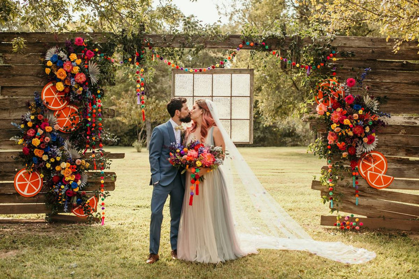 bride and groom stand in front of colorful rainbow wedding theme ceremony backdrop with life-size paper orange slices, pom pom garlands and flowers in rainbow colors