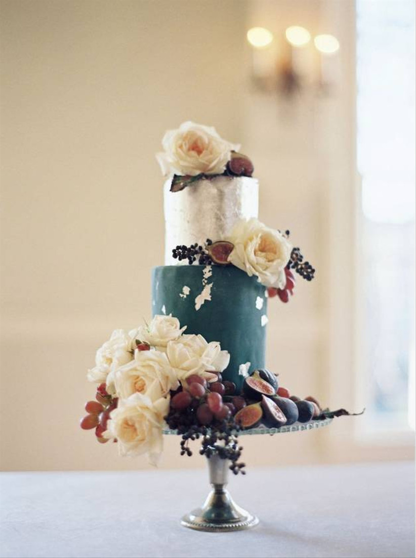 dark teal and silver wedding cake decorated with large white flowers and fresh fruit