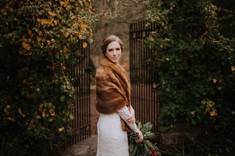 bride wearing lace wedding dress with long sleeves and brown fur wrap