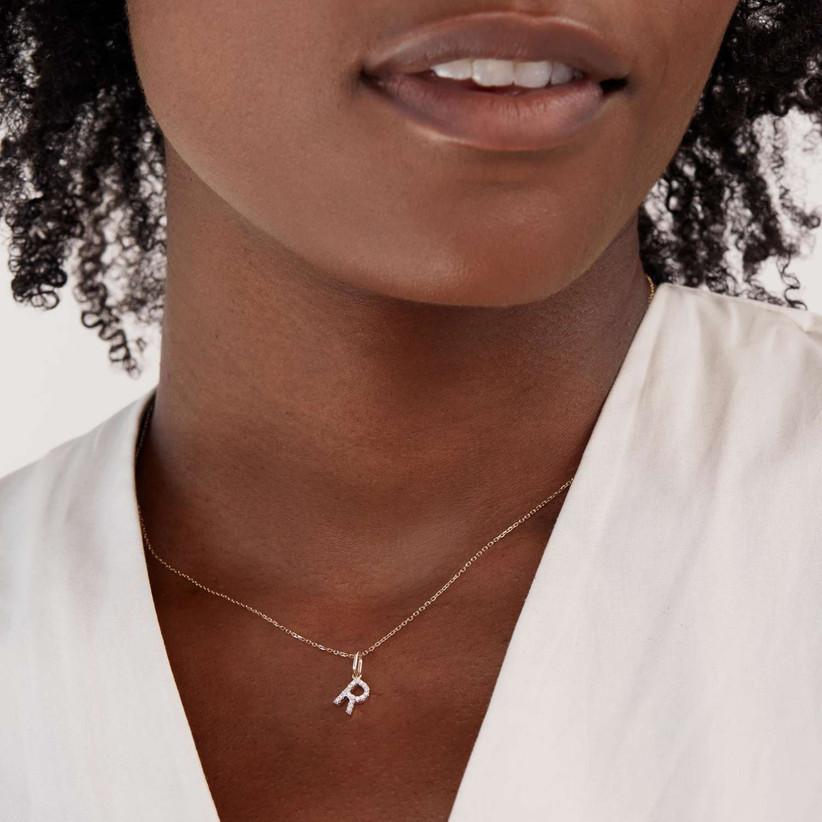 Diamond initial necklace around woman's neck