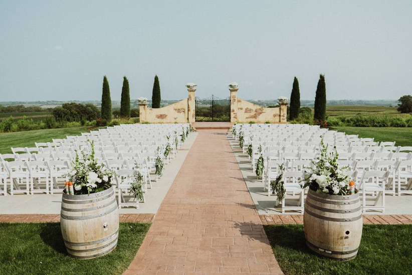 european-style outdoor wedding ceremony with stone gates at altar surrounded by cypress trees