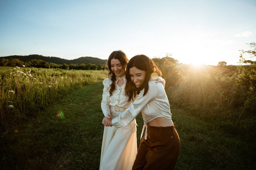 same-sex female couple walks through a scenic wildflower field during golden hour