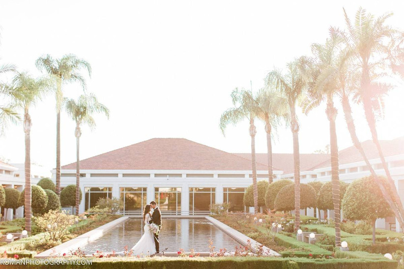 bride and groom in romantic photo with palm tree backdrop