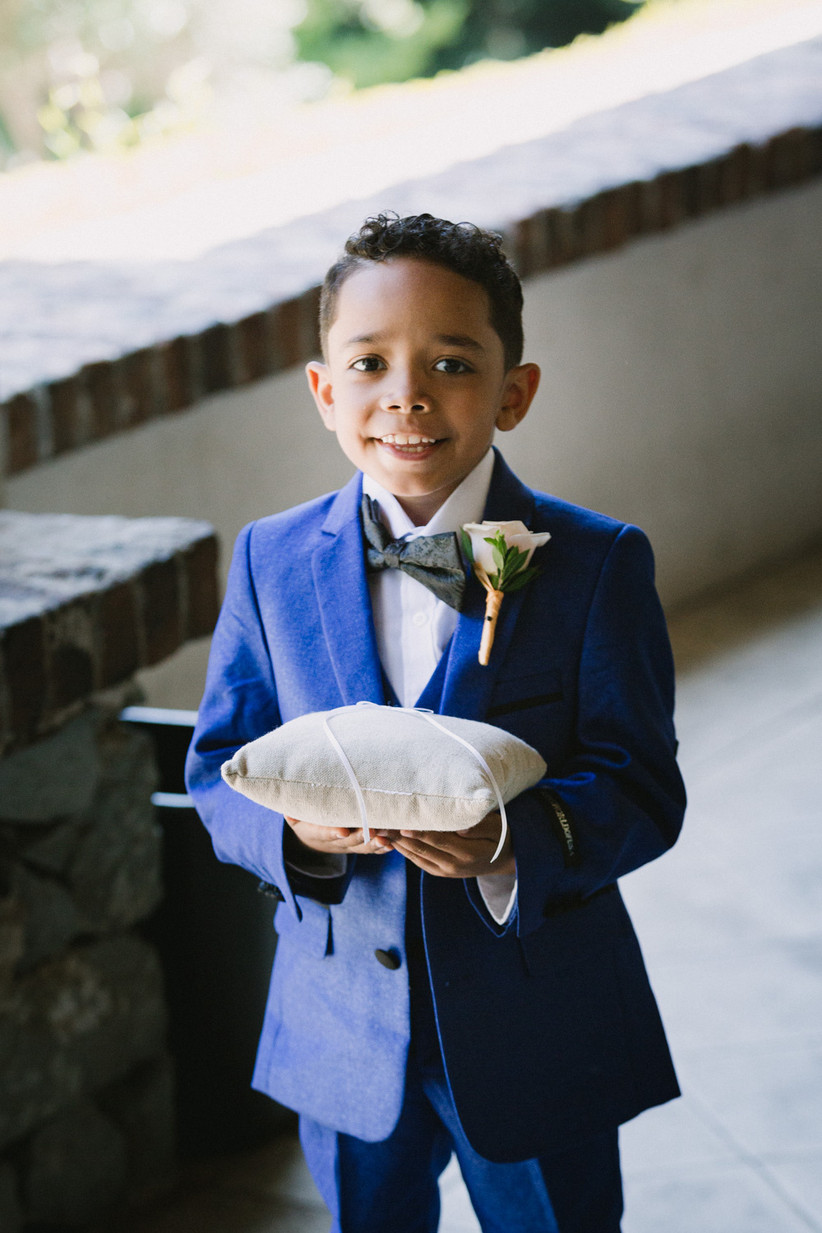 ring bearer wearing a navy blue suit smiles as he holds the ring pillow