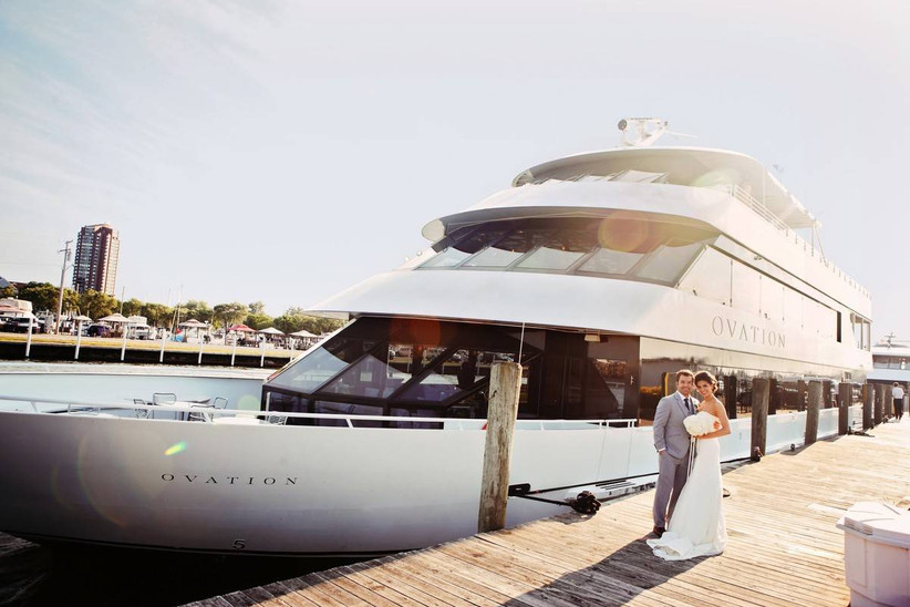 bride and groom posing in front of yacht