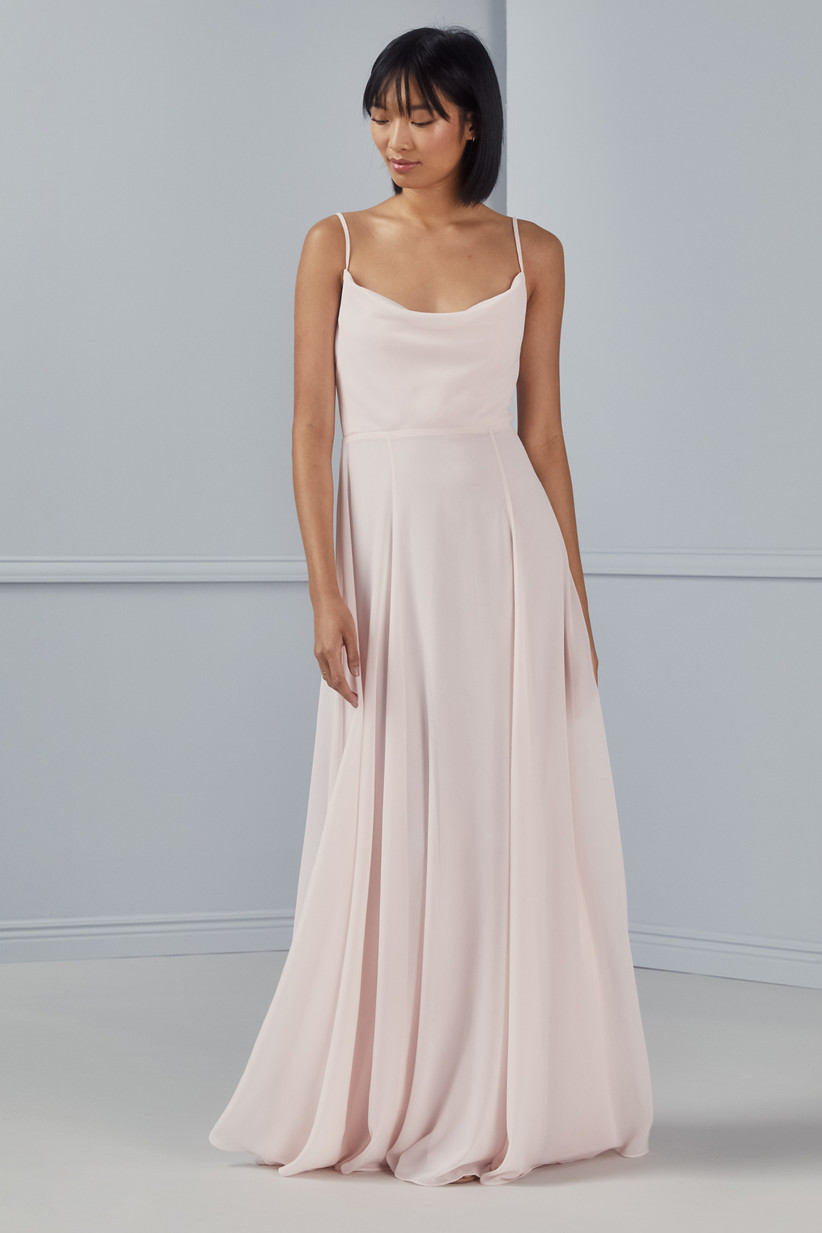 Model wears light blush bridesmaid dress trend with cowl neckline and spaghetti straps