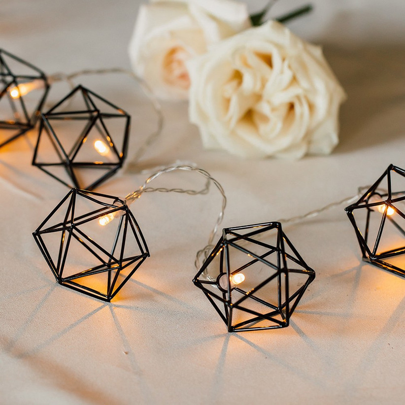 Black geometric string lights draped on guest table