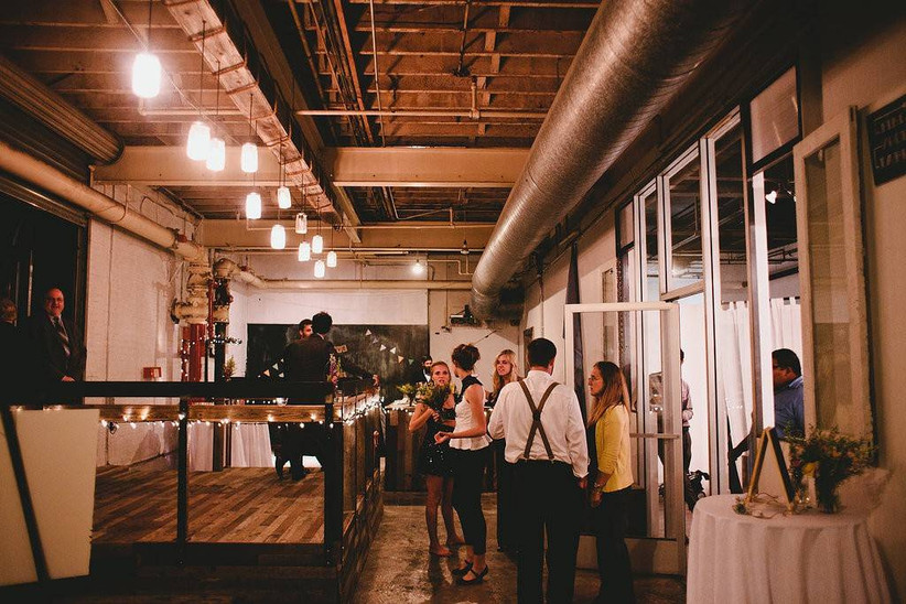 industrial space with exposed pipework and people enjoying reception