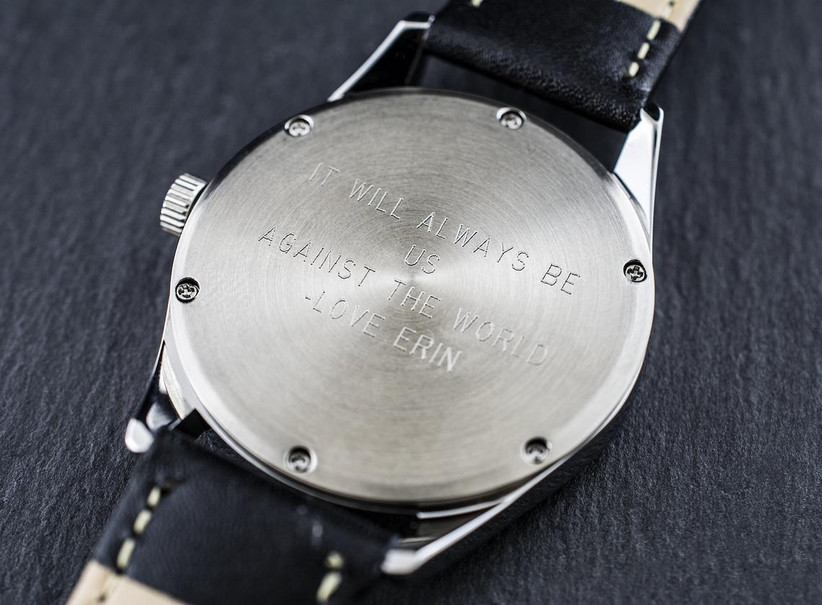 Minimalist leather-strap watch turned over to show engraved back that reads It Will Always Be Us Against the World