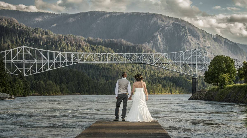 bride and groom hold hands while standing on a dock overlooking lake and bridge in the distance